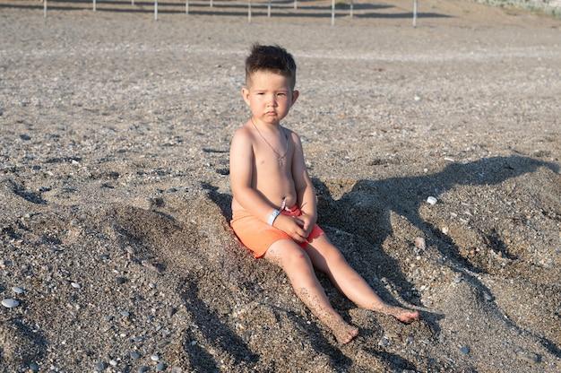 화창한 날 해변에서 노는 심각한 유아 소년.