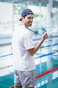 Serious trainer looking at stopwatch at the pool