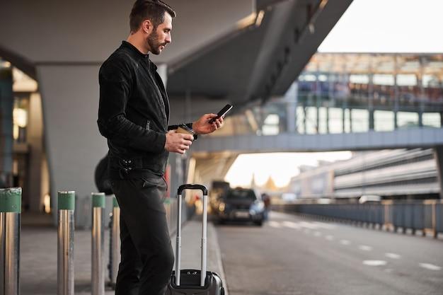 야외에서 스마트폰과 커피를 들고 있는 진지한 여행자