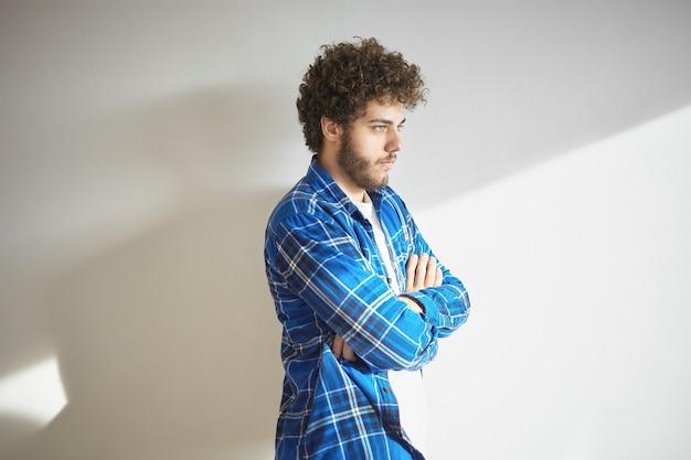 白い壁に孤立して立っている、不承認または不本意の兆候として胸に腕を組んでいるファジーなひげを持つ深刻なトレンディなヒップスターの男。人間の表情とボディーランゲージ