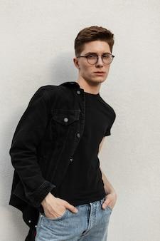 세련 된 안경에 유행 데님 옷에 심각한 유행 젊은이 따뜻한 봄 날에 거리에 빈티지 건물 근처 쉬고있다. 잘 생긴 미국 남자 모델 야외. 캐주얼 남성복.