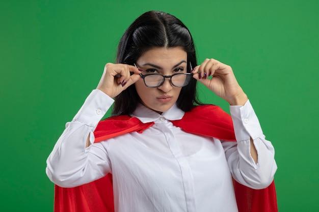 Ragazza seria ingannevole giovane supereroe caucasico con gli occhiali che tengono i vetri nelle mani con sguardo sospettoso isolato sulla parete verde