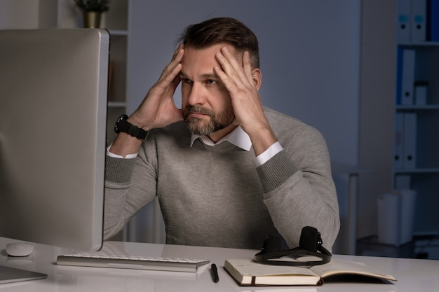 Serious and troubled office worker touching head while working in front of computer screen