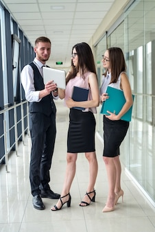 真面目な2人の実業家と1人の男性が書類を見せ、オフィスの廊下で部下に間違いについて話します。会議のコンセプト