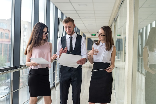 Serious two businesswoman and one men show document and talk about mistake to subordinate  in office hallway. meeting concept