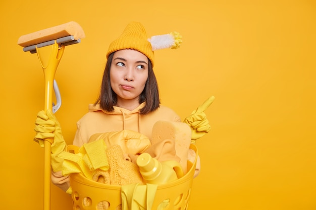 캐주얼웨어에 심각한 감정적 인 아시아 여성 가정부는 빈 복사본 공간에서 나타냅니다 청소는 집안일을 정기적으로 노란색 배경 위에 절연 제품 청소에 대한 프로모션을 보여줍니다