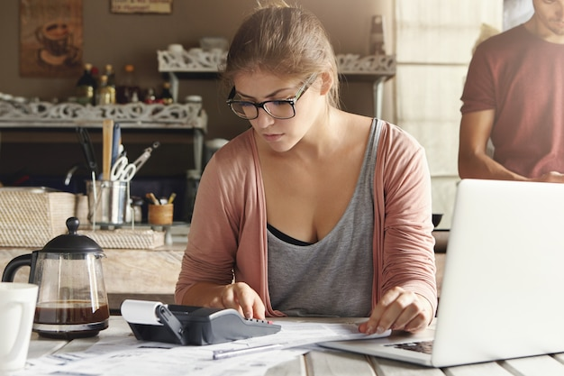 Serious unhappy young female in glasses sitting at kitchen table with open laptop pc and calculator on it while calculating finances. housewife using electronic devices for paying utility bills online