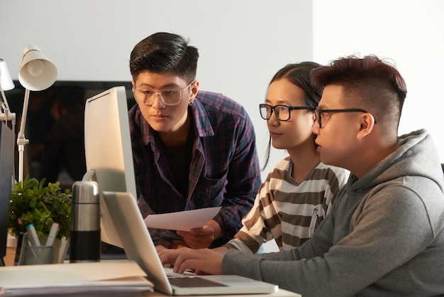 眼鏡をかけている真面目な大学生が、自分たちが取り組んでいる新しいプログラムをテストし、コンピューターの画面を見ている