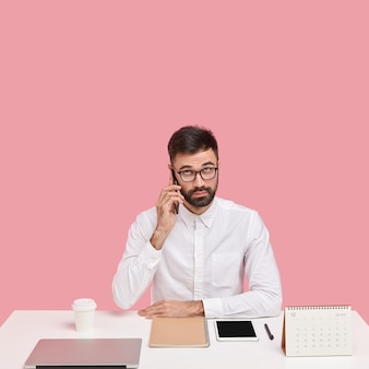 Un uomo intelligente con la barba lunga seria chiama il servizio clienti, ha una conversazione telefonica in pausa dal lavoro, vestito con una camicia bianca, concentrato verso l'alto