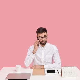 Серьезный небритый интеллигентный мужчина звонит в службу поддержки, разговаривает по телефону в перерыве на работе, одет в белую рубашку, смотрит вверх