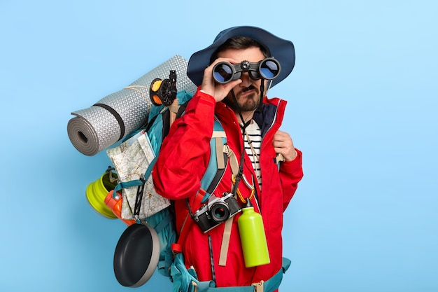 Serious unshaven male backpacker keeps binoculars near eyes, wears hat and red jacket, explores new way, carries tourist backpack