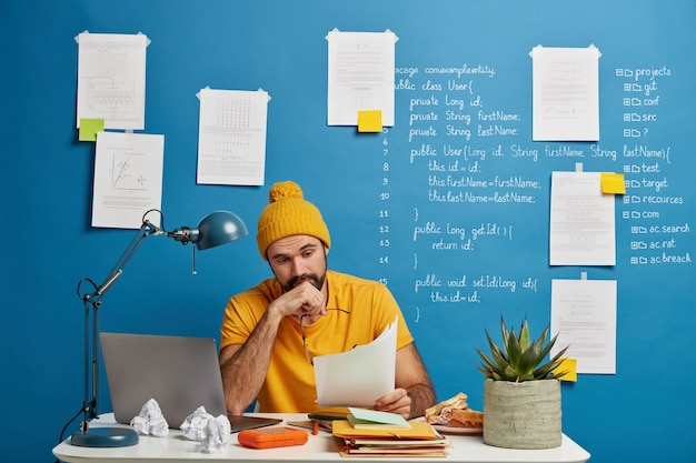 Serious unshaven male manager in yellow outfit looks through financial documentation