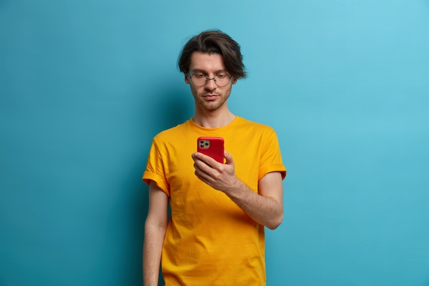 Serious unshaven man holds cell phone in hand, concentrated in screen, watches tutorial video, types answer or reads feedback about new project, wears transparent glasses, isolated on blue wall