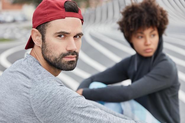 Серьезный небритый мужчина в стильной красной кепке, сером свитере, любит досуг, дышит свежим воздухом, афро-девушка на заднем плане