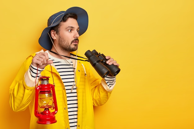 Serious unshaven man observes something with binoculars, holds red oil lamp, walks on foot, explores new place, wears hat and raincoat, isolated over yellow wall