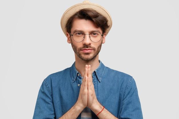 Серьезный небритый мужчина со спокойным выражением лица, стоит в молитвенном жесте, просит прощения, одет в джинсовую рубашку