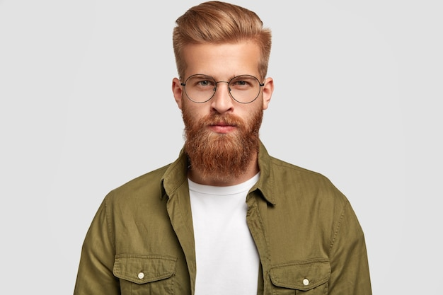 Серьезный небритый мужчина с рыжими волосами и бородой смотрит прямо, о чем-то думает, носит модную рубашку и круглые очки, изолированные на белой стене. концепция мужественности
