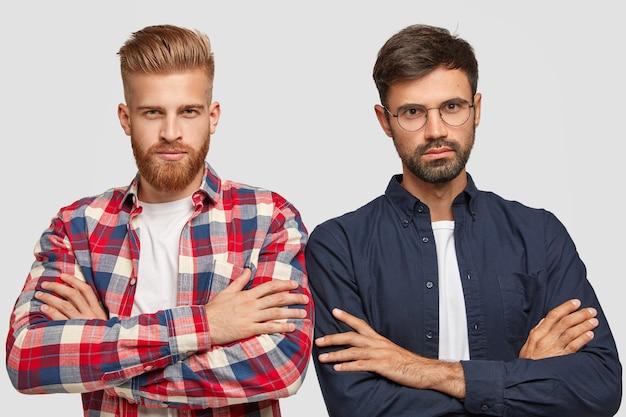 真面目な無精ひげを生やした2人のハンサムな男性の同僚または同僚が肩を並べて立って、手を組んで、自信を持って見て、企業の仕事の準備ができて、白い壁に隔離されています。