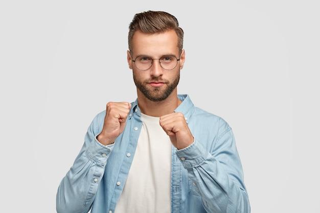 真面目な無精ひげを生やした若い男性は、自分を守る準備ができている拳を見せ、エレガントな青いシャツ、眼鏡をかけ、白い壁に向かってポーズをとります。自信のあるあごひげを生やした男が誰かと戦う。メンズストレングス