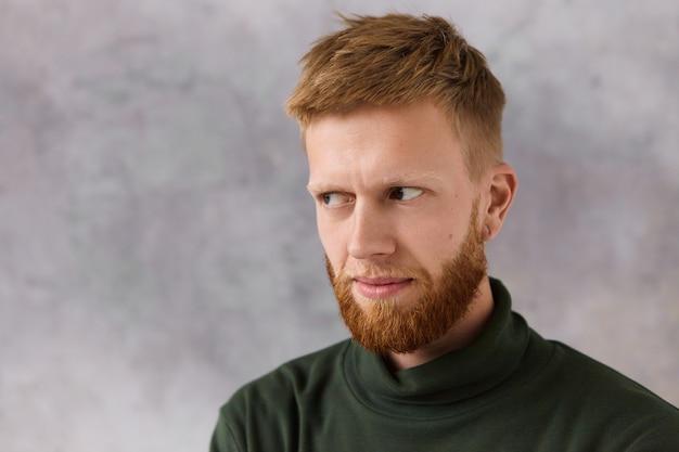 의심을 표현하는 세련된 짙은 녹색 터틀넥 스웨터에 심각한 형태가 이루어지지 않은 젊은 남자가 눈썹 아래에서 멀리보고 있습니다. 강렬한 표정을 가진 수염 포즈와 잘 생긴 남자
