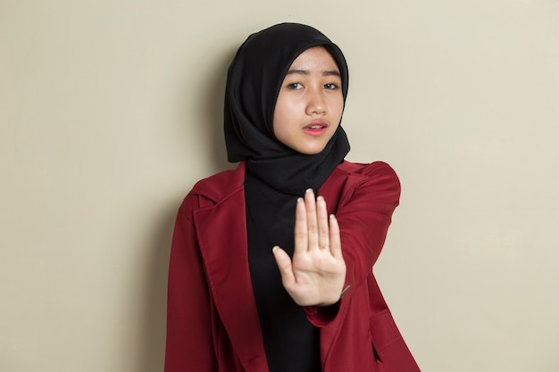 Serious upset asian muslim woman showing stop hand gesture