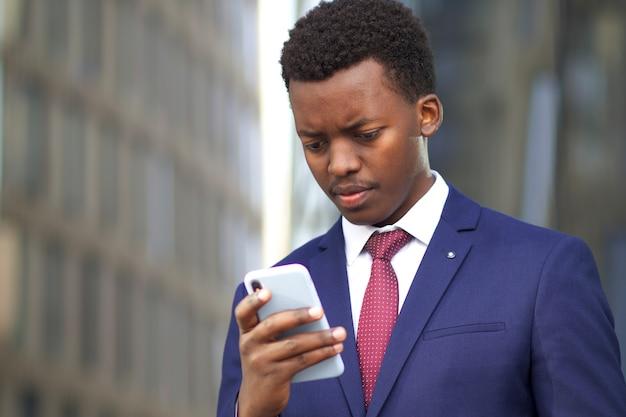 深刻な動揺の欲求不満のアフリカ系アメリカ人のビジネスマンは眉をひそめ、彼の携帯電話のスマートフォンを見て、否定的なニュースを読んでいます。