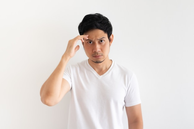 Serious and upset man wears white tshirt isolated on white wall