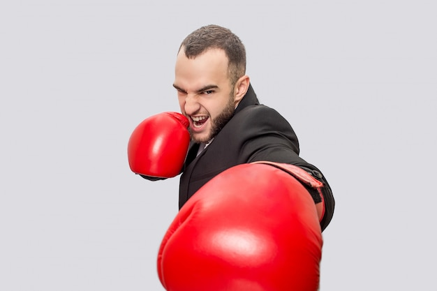 Serious and well-built man in suit wears box gloves. he stand in pose. guy screams. he is ready to beat.