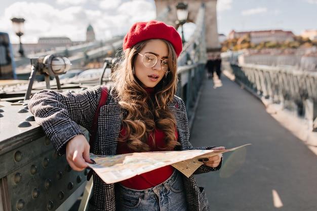 街の背景に立っている地図を見て深刻な白人女性旅行者