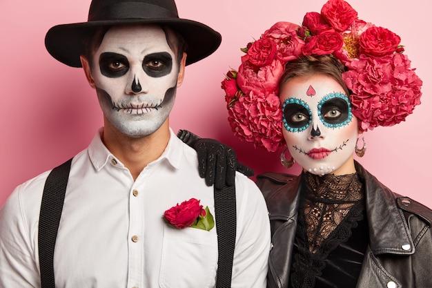 真面目な女性と男性は伝統的なメキシコのイメージを持っており、砂糖の頭蓋骨を身に着け、衣装パーティーのための特別な服を着て、近くに立って、ピンクの背景の上に隔離されています。