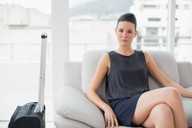 Serious woman in black dress sitting on sofa