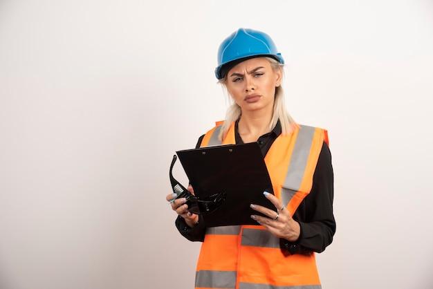 クリップボードを保持しているヘルメットを持つ深刻な女性ビルダー。高品質の写真