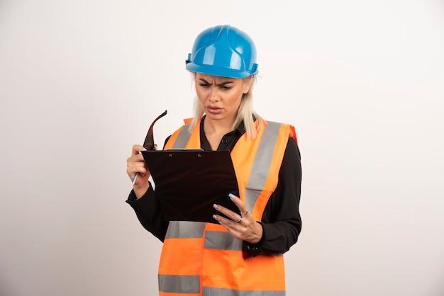 クリップボードを見ているヘルメットを持つ深刻な女性ビルダー。高品質の写真