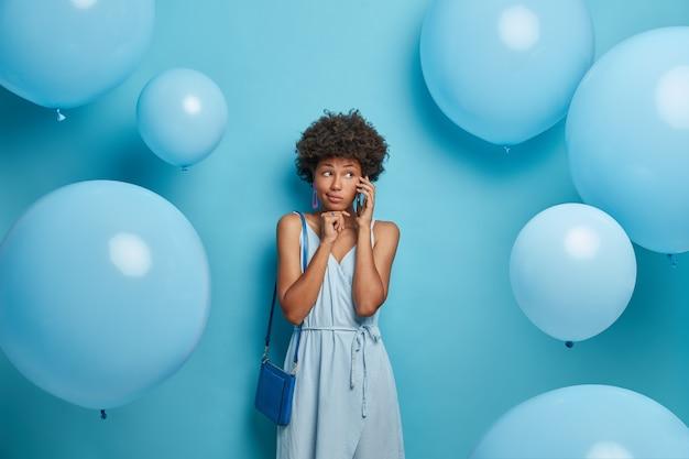 Una donna seria chiama un amico, tiene lo smartphone vicino all'orecchio, farà una passeggiata nel parco, indossa un vestito blu e una borsa per adattarsi al vestito, invita qualcuno alla festa, si prepara per la celebrazione, si trova vicino ai palloncini