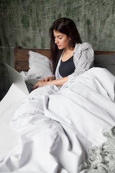 Serious woman checking news online on bed in the morning