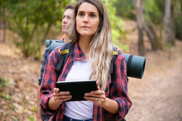 Серьезная женщина, проверяющая путь через планшет и идущая по горной тропе. кавказские туристы или путешественники с рюкзаками и походы в лес. походный туризм, приключения и концепция отпуска