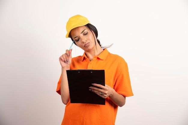 Corriere serio della donna con la matita che considera la lavagna per appunti sulla parete bianca.