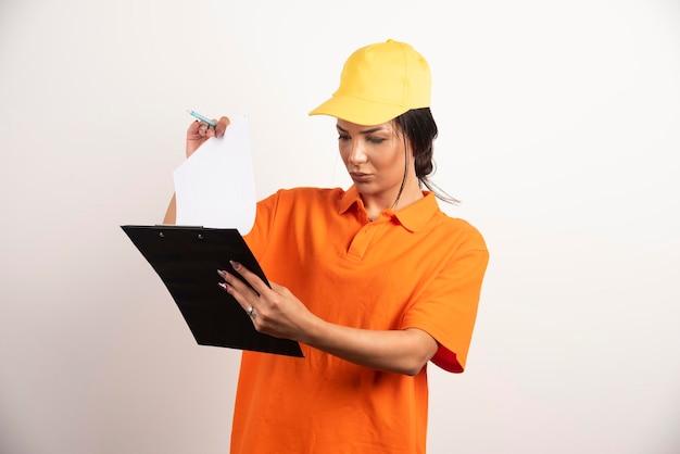 白い壁のクリップボードを見ている鉛筆で深刻な女性の宅配便。