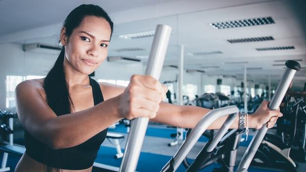Serious woman doing an elliptical machine