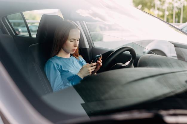 차 안에 앉아있는 동안 그녀의 스마트 폰을 들고 심각한 여자.