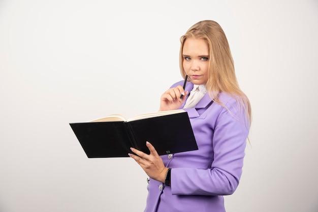 白い背景の上の開いたタブレットを保持している深刻な女性。高品質の写真
