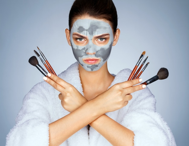 Serious woman holding up make-up brushes
