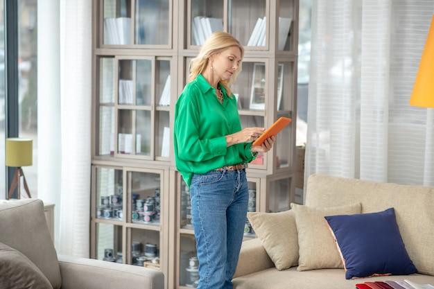 유리 도어와 밝은 캐비닛 근처에 서있는 그녀의 손에 오렌지 타블렛으로 녹색 셔츠에 심각한 여자.
