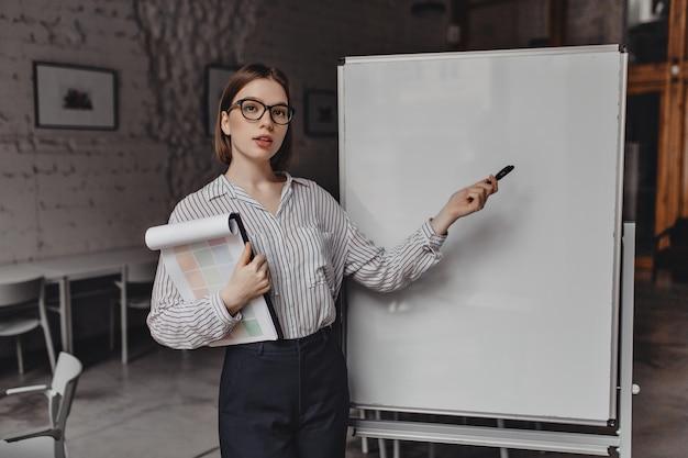검은 바지와 줄무늬 셔츠를 입은 진지한 여성이 비즈니스 상태에 대해 이야기하고 보드에서 마커를 가리키며 보고서를 보관합니다.