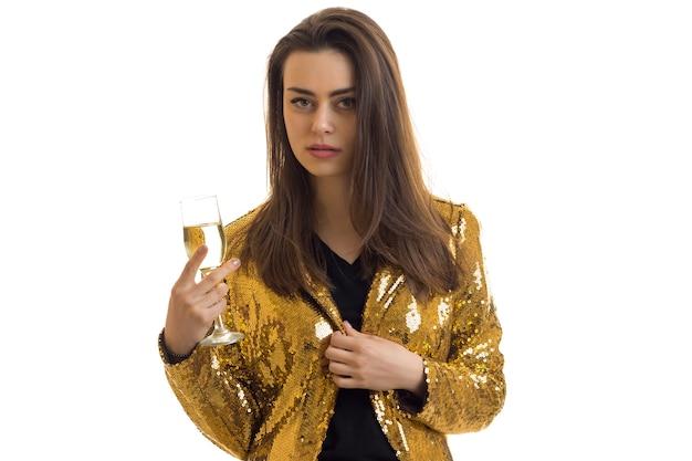 白で隔離手にワイングラスと金色のジャケットの深刻な女性