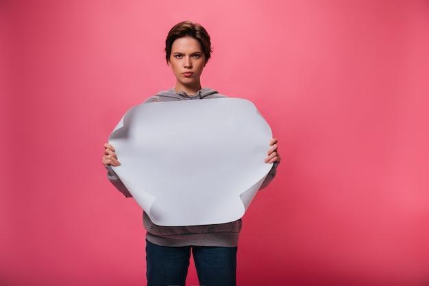 パーカーの真面目な女性は、テキストの場所で白い紙を保持しています。ピンクの孤立した背景にポーズをとってジーンズの短い髪の少女の肖像画