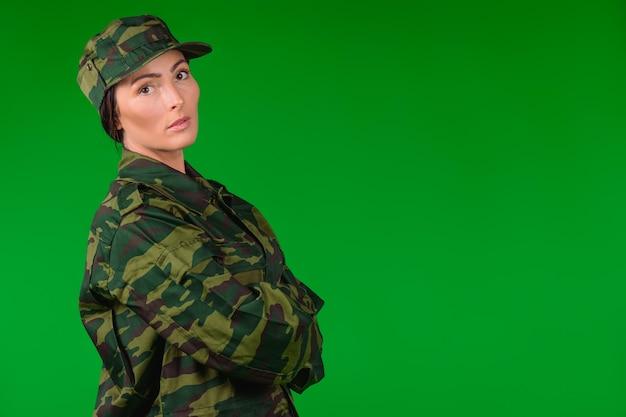 군복에 심각한 여자는 카메라를 살펴 봅니다. 녹색 배경과 빈 쪽 광고 공간.