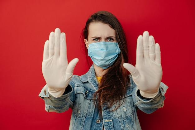 滅菌フェイスマスク手袋の深刻な女性は、停止ジェスチャーでカメラに向かって手を引っ張って、制限を示し、赤い背景に分離されたデニムジャケットを着ています。検疫パンデミックコロナウイルスウイルスの概念