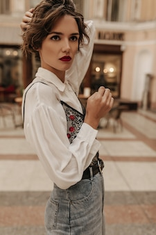 흰색 셔츠와 청바지 블랙 벨트 도시에서 멀리 찾고 심각한 여자. 거리에서 포즈를 취하는 밝은 입술과 갈색 머리 여자.