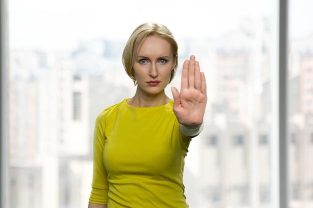 真面目な女性が停止ジェスチャーを示しています